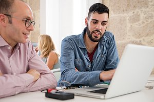 Two men sitting in front of a laptop