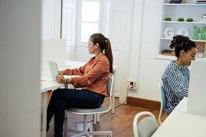 Two women sitting in an office worki