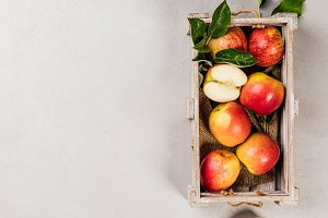 Ripe organic apples in wooden tray
