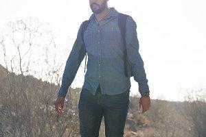 Man walking over rocks in the desert