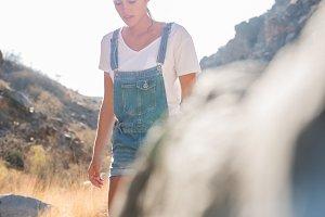 Woman walking past rocks in the moun