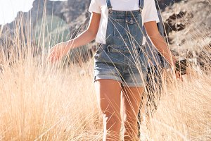 Woman walking in the long grass hold