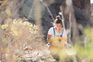 Woman sitting on a rock reading in t