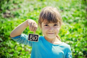 bio farm sign in the hands of a kid.