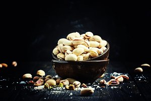 Salted pistachios in a bowl, black b