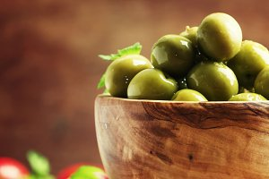 Green olives in a wooden bowl, selec