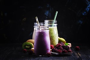 Berry smoothies in bottles, gray bac