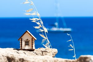 Toy house against the blue sea. Them
