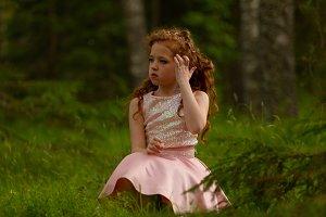 Little emotional girl walks in a sum