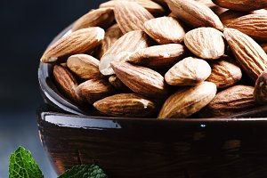 Almonds in a bowl, black background,