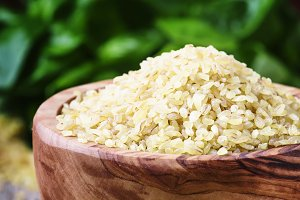 Raw barley bulgur in a wooden bowl,