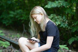 Teenager girl sitting on the railway