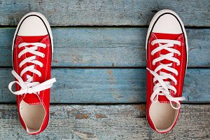 Red retro sneakers on a blue wooden
