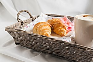 croissants, coffee cup, flower in ro