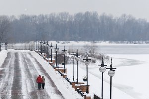 couple walking on snowy park alley a