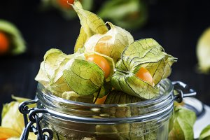 Physalis in a glass jar, dark backgr