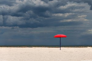 One red parasol on a sandy beach aga