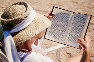 adult woman in a hat on a beach read