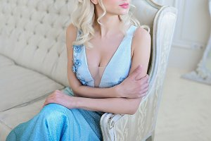 Blonde woman in blue dress sits