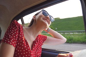 Happy girl in sunglasses leaning out