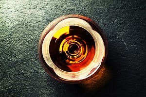 Cognac in a glass on black stone bac