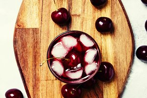 Cold sweet cherry juice with ice cub