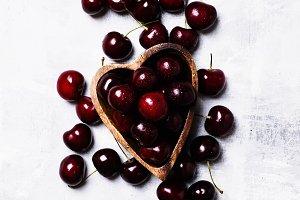 Black sweet cherries in bowl in shap
