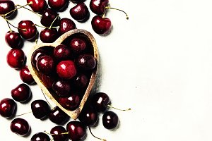 Fresh black cherries in wooden bowl,