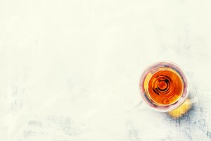 Cognac on gray background, top view