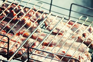 Meat on the grill cooking on the coa