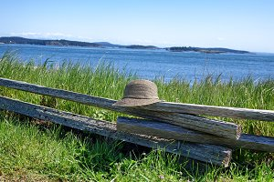 Hat on weathered fence with Ocean