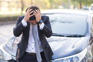 Businessman with breakdown car