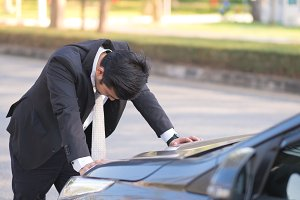 Businessman with breakdown car