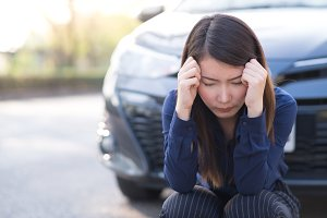 Young woman with broken down car