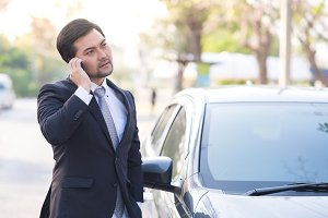 Businessman using a mobile at car