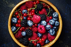 Summer berries in wooden bowl, black
