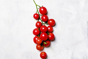 Red cherry tomatoes on the vine, gra