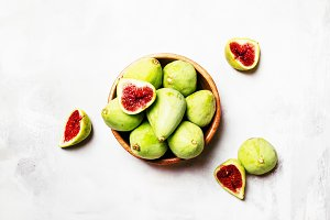 Sweet green figs in wooden bowl, gra