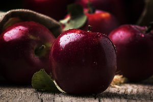 Small red apples on vintage wooden b