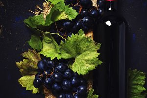 Red wine in bottle and grapes, black