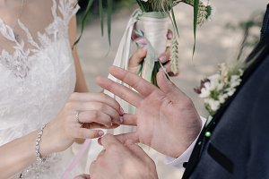 bride puts ring on groom's hand