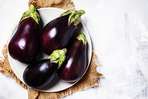 Fresh purple eggplants on plate, top