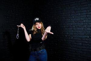 FBI female agent in cap and with gun