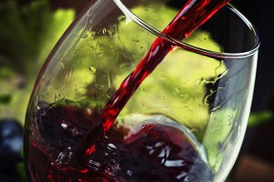 Red wine pouring into a glass, vinta