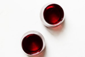 Red wine in glasses on a white backg