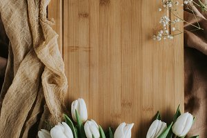 top view of white tulips on wooden b
