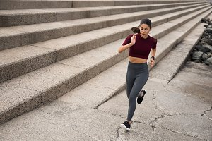 Sporty young woman running on stairs