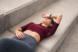 Sporty young brunette lying on stair