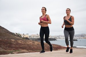 Two pretty girls running in fitness