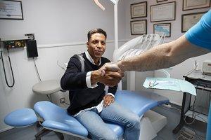 Content black man greeting dentist